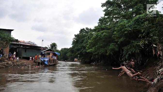 Anak-anak berenang di Kali Ciliwung, Bukit Duri, Jakarta, Kamis (12/4). Relokasi bangunan liar di sekitar kali nantinya bakal dilakukan untuk mengembalikan fungsinya. (Merdeka.com/Iqbal Nugroho)