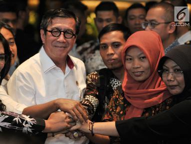 Menkumham Yasonna Laoly (tengah) bersama terpidana kasus pelanggaran ITE Baiq Nuril (dua kanan) dan lainnya bersalaman usai mengadakan pertemuan di Kantor Menkumham, Jakarta, Senin (8/7/2019). Pertemuan Baiq Nuril dan Yasonna Laoly untuk membahas pemberian amnesti. (merdeka.com/Iqbal Nugroho)