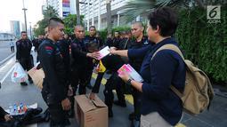 Relawan TKN Jokowi-Ma'ruf Amin membagikan multivitamin kepada aparat kepolisian yang melakukan penjagaan di Bundaran HI, Jakarta, Jumat (24/5/2019). Mereka juga membagikan makanan berbuka puasa sebagai bentuk kepedulian untuk aparat yang telah menjaga keamanan di Jakarta. (Liputan6.com/Angga Yuniar)