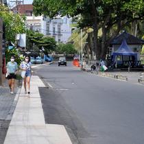 Pejalan kaki berjalan di sepanjang jalan utama yang sepi saat Pemberlakuan Pembatasan Kegiatan Masyarakat (PPKM) Level 3 di Kuta, Badung, Bali, Jumat (23/7/2021). Pemprov Bali tengah menerapkan PPKM Level 3. (SONNY TUMBELAKA/AFP)