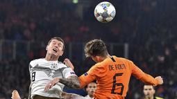 Pemain Belanda, Marten de Roon, duel udara dengan gelandang Jerman, Toni Kroos, pada laga UEFA Nations League di Veltins Arena, Gelsenkirchen, Senin (19/11/2018). Kedua tim bermain imbang 2-2. (AP/Martin Meissner)