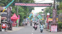 """Pengendara melintasi gapura """"Kampoeng Ramadhan Jogokariyan"""" di Jalan Jogokaryan Yogyakarta, Senin (21/5). Kampoeng Ramadhan Jogokaryan adalah salah satu program dari masjid Jogokariyan untuk menyemarakan bulan suci Ramadan. (Liputan6.com/Gholib)"""