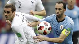 Striker Prancis, Antoine Griezmann, berebut bola dengan bek Uruguay, Diego Godin, pada laga perempat final Piala Dunia di Stadion Nizhny Novgorod, Nizhny Novgorod, Jumat (6/7/2018). Prancis menang 2-0 atas Uruguay. (AP/Natacha Pisarenko)