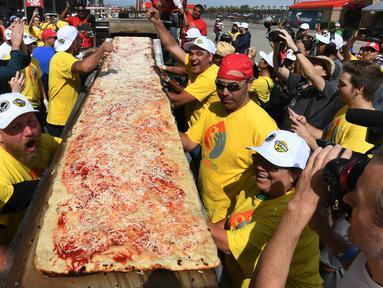 Peserta menunjukan pizza yang telah selesai dibuat di jalur Auto Club Speedway, di Fontana, California (10/6). Mereka berhasil memecahkan rekor Guinness World Records untuk pizza terpanjang di dunia dengan panjang 1,32 mil atau 2,13 km. (AFP/Mark Ralston)