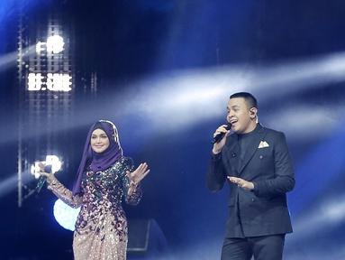 Penyanyi Siti Nurhaliza (kiri) berduet dengan Tulus dalam konser 'Dato Sri Siti Nurhaliza on Tour' di Istora Senayan, Jakarta, Kamis (21/2). Kehadiran Tulus menjadi kejutan spesial bagi penonton konser tersebut. (Fimela.com/Bambang E Ros)