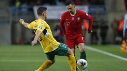 Bek Portugal, Mario Rui berusaha melewati pemain Lithuania, Saulius Mikoliunas pada pertandingan Grup B Kualifikasi Piala Eropa 2020 di stadion Algarve di luar Faro, Portugal (14/11/2019). Portugal menang besar 6-0 atas Lithuania. (AP Photo/Armando Franca)