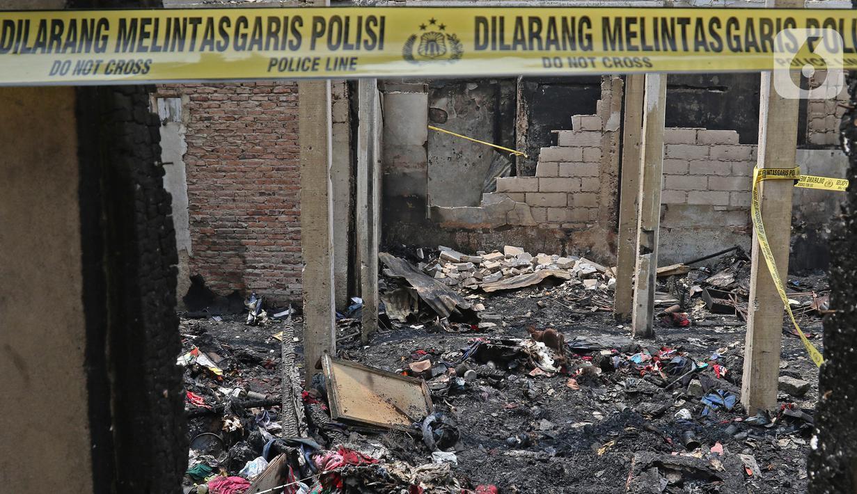 Garis polisi dipasang di sisa permukiman yang terbakar di Jalan Keadilan Dalam, Taman Sari, Jakarta Barat, Senin (19/4/2021). Kebakaran permukiman padat tersebut mengakibatkan sebanyak 200 rumah hangus terbakar dan sekitar 1.000 warga terpaksa mengungsi. (Liputan6.com/Herman Zakharia)