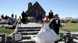Sepasang suami istri meninggalkan Gereja setelah upacara pernikahan mereka di Danau Tekapo, Selandia Baru (6/10). Danau ini merupakan tujuan wisata yang populer dan terdapat beberapa hotel di kota kecil tersebut. (AP Photo/Mark Baker)