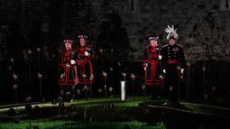 Yeoman Warders atau 'Beefeaters' bersiap menyalakan ribuan lilin di parit kering Tower of London, Inggris, Selasa (6/11). Nyala lilin membentuk instalasi yang disebut 'Beyond the Deepening Shadow: The Tower Remembers'. (AP Photo/Alastair Grant)