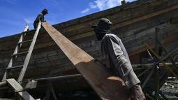 Pekerja memuat material untuk membuat kapal nelayan di Banda Aceh, Aceh pada 21 November 2020. Industri galangan kapal tradisional di daerah itu mengalami kesulitan memperoleh bahan baku kayu untuk memproduksi kapal nelayan, sehingga berdampak pada proses penyelesaian kapal. (CHAIDEER MAHYUDDIN/AFP)