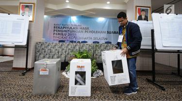 Panitia membawa kotak suara saat proses rekapitulasi penghitungan suara Pemilu 2019 tingkat Kota Jakarta Selatan di Hotel Maharaja, Jakarta, Selasa (7/5/2019). Proses penghitungan suara diselenggarakan selama tiga hari. (Liputan6.com/Herman Zakharia)