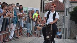 Seorang pria menunggangi keledai dalam kompetisi balap keledai tradisional ke-53 di Tribunj, Kroasia (29/8/2020). (Xinhua/Pixsell/Hrvoje Jelavic)