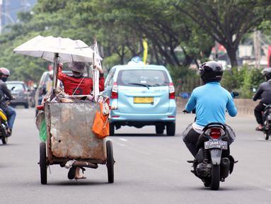 Tuna wisma menarik gerobaknya saat melintas di Jalan Margonda Raya, Depok, Kamis (16/4/2020). Pandemi COVID-19 memberikan dampak yang sangat besar bagi sosial dan ekonomi Indonesia. Bahkan yang paling dikhawatirkan bertambahnya angka kemiskinan dan pengangguran. (Liputan6.com/Helmi Fithriansyah)