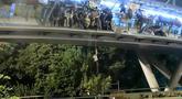 Demonstran menuruni jembatan menggunakan tali untuk melarikan diri dari Universitas Politeknik Hong Kong di Distrik Hung Hom, Hong Kong, Senin (18/11/2019). Lusinan demonstran melarikan diri dari Universitas Politeknik Hong Kong yang dikepung polisi selama berhari-hari. (AP Photo/Kin Cheung)