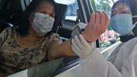 Warga lanjut usia (lansia) melakukan cek kesehatan saat vaksinasi Covid-19 secara drive-thru di area parkir Hall C JIExpo Kemayoran, Jakarta, Rabu (3/3/2021). Kementerian Kesehatan berkolaborasi bersama sejumlah mitra dalam layanan vaksinasi drive thru tersebut. (Liputan6.com/Herman Zakharia)