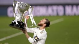 Kapten Real Madrid Sergio Ramos mengangkat piala saat merayakan kemenangan La Liga musim 2019/20 usai menaklukkan Villarreal di Estadio Alfredo Di Stefano, Kamis (16/7/2020). Real Madrid memastikan diri menjadi juara Liga Spanyol setelah mengalahkan Villarreal 2-1. (AP Photo/Bernat Armangue)