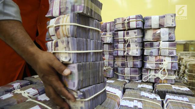 """Petugas menata tumpukan uang kertas di ruang penyimpanan uang """"cash center"""" BNI, Jakarta, Kamis (6/7). Tren negatif mata uang Garuda berbanding terbalik dengan Indeks Harga Saham Gabungan (IHSG) yang mulai bangkit ke zona hijau (Liputan6.com/Angga Yuniar)"""