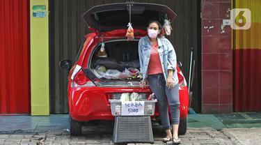 Cynthia (28) mahasiswi perguruan tinggi swasta menunggu pembeli di Jalan Santosa, Depok, Jawa Barat, Kamis (21/5/2020). Cynthia menggunakan mobil pribadinya sebagai lapak berjualan berbagai macam sayuran dengan harga serba Rp 5.000. (Liputan6.com/Herman Zakharia)