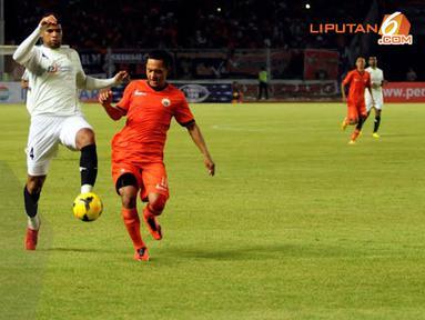 Penyerang Persija Rahmad Afandi tidak gentar sedikit pun saat berebut bola dengan pemain belakang PDRM FA Malaysia yang bertubuh tinggi besar Rafael Souza (Liputan6.com/ Helmi Fithriansyah)