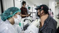 Petugas medis menyuntikkan vaksin COVID-19 Astrazeneca kepada pekerja ritel di GOR Tanjung Duren, Jakarta Barat, Senin (24/5/2021). Berdasarkan data Kementerian Kesehatan hingga 23 Mei 2021, sebanyak 14.890.933 orang telah menerima vaksin COVID-19 dosis pertama. (Liputan6.com/Faizal Fanani)