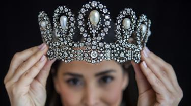 Karyawan Sotheby memamerkan mahkota berlian dan mutiara yang diwariskan dari generasi ke generasi keluarga kerajaan Italia selama pratinjau di Sotheby, Jenewa, Swiss, Kamis (6/5/2021). Periasan diperkirakan terjual antara 1 - 1,5 juta USD pada lelang 11 Mei 2021. (Martial Trezzini/Keystone via AP)