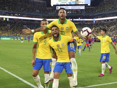 Penyerang Brasil, Neymar Jr (10) berselebrasi dengan rekannya Dani Alves (13) dan Richarlison (9) usai mencetak gol ke gawang Kolombia selama laga uji coba di Hard Rock Stadium, Florida (7/9/2019). Gol neymar pada menit ke-58 ini menjadi penyelamat Brasil. (David Santiago/Miami Herald via AP)