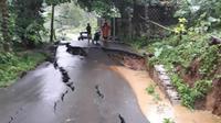Jalan penghubung antara Kecamatan Babakan Madang dengan Sukamakmur, Kabupaten Bogor, Jawa Barat ambles, Selasa (31/12/2019) sore. (Liputan6.com/Achmad Sudarno)