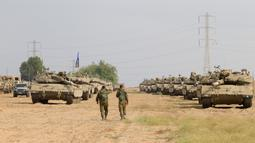 Tentara Israel berjalan melewati tank di dekat perbatasan Gaza-Israel, Jumat (19/10). Pengerahan kekuatan militer terjadi berselang sehari usai roket Palestina menghancurkan sebuah rumah di selatan Israel. (AP Photo/Ariel Schalit)