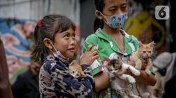 Warga mengantre membawa hewan peliharaannya untuk diperiksa kesehatannya di Kawasan Tebet, Jakarta, Senin (22/2/2021). Dinas KPKP Provinsi DKI Jakarta mengadakan pemeriksaan kesehatan hewan peliharaan secara gratis bagi yang terdampak banjir. (Liputan6.com/Faizal Fanani)