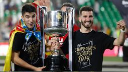 Dua pemain Valencia berpose dengan trofi Copa Del Rey usai pertandingan melawan Barcelona pada babak final di stadion Benito Villamarin di Seville, Spanyol (25/5/2019). Barcelona kalah 1-2 dari Valencia lewat gol Kevin Gameiro dan Rodrigo. (AP Photo/Miguel Morenatti)