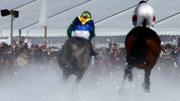 Penonton menyaksikan peserta memacu kudanya saat lomba Flat Course selama pacuan kuda White Turf di danau beku, Saint Moritz, Swiss, 17 Februari 2019. Pacuan kuda ini diadakan pada Februari ketika danau St. Moritz masih beku. (STEFAN WERMUTH / AFP)