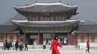 Seorang wanita mengenakan masker berjalan di Gerbang utama Istana Gyeongbok, Seoul, Korea Selatan, Sabtu (22/2/2020). Di Korea Selatan hingga kini sudah ada dua kematian akibat virus corona. (AP Photo/Lee Jin-man)