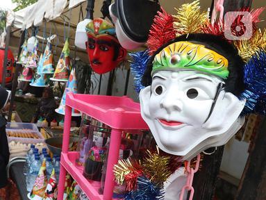 Sejumlah anak melihat topeng saat mengunjungi Festival Tugu Pancoran di Jakarta, Minggu (1/12/2019). Festival Tugu Pancoran yang digelar setiap setahun sekali ini indetik dengan budaya betawi. (Liputan6.com/Herman Zakharia)