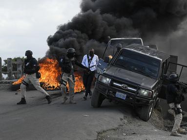 Polisi meninggalkan kendaraan mereka saat demonstrasi yang berubah menjadi kekerasan di Cap-Haitien, Haiti, Kamis (22/7/2021). Demonstrasi menuntut keadilan atas pembunuhan Presiden Haiti Jovenel Moise terus berlanjut dan menimbulkan kerusuhan. (AP Photo/Matias Delacroix)