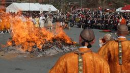 "Biksu Buddha berdoa di depan kobaran api saat festival berjalan di atas api atau dikenal sebagai ""Nagatoro Hi-Matsuri,"" di kuil Fudoji, kota Nagatoro, Jepang, Minggu (5/3). Festival ini diadakan untuk menyambut datangnya musim semi. (Kazuhiro NOGI/AFP)"