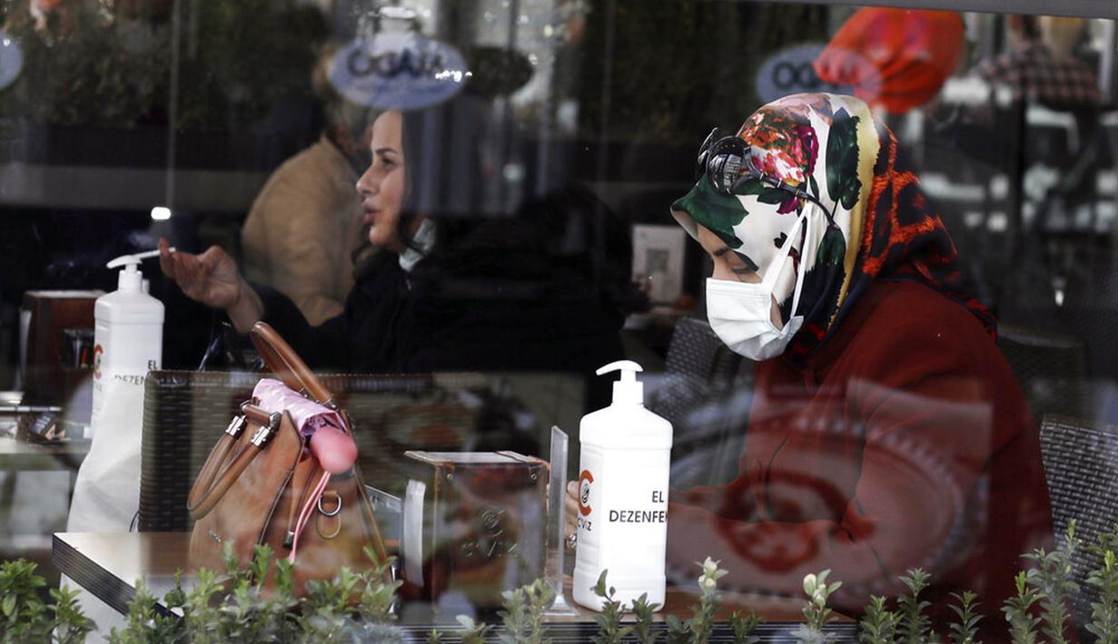 Seorang wanita yang mengenakan masker untuk membantu melindungi dari penyebaran COVID-19 duduk dalam kafe di Ankara, Turki, Selasa (30/3/2021). Turki kembali memberlakukan lockdown akhir pekan dan pembatasan selama Ramadan menyusul peningkatan tajam kasus COVID-19. (AP Photo/Burhan Ozbilici)