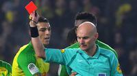 Wasit Tony Chapron (kanan) memberikan kartu merah kepada pemain Nantes, Diego Carlos, pada laga kontra Paris Saint-Germain di Stade de la Beaujoire - Louis Fonteneau, Nantes, Minggu (14/1/2018). (AFP/Loic Venance)
