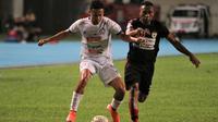 Gelandang Arema, Dendi Santoso, dihadang striker Persipura, Titus Bona, dalam pertandingan di Stadion Aji Imbut, Tenggarong, Minggu (20/10/2019). (Bola.com/Iwan Setiawan)