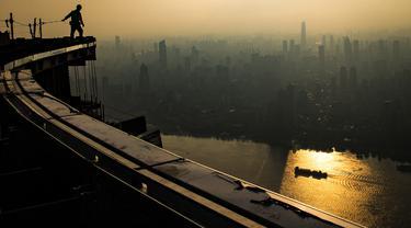 Seorang pekerja konstruksi bekerja di ketinggian sekitar 500 meter di lokasi pembangunan sebuah bangunan bertingkat tinggi di Wuhan, Provinsi Hubei, China tengah (11/8/2020). Para pekerja konstruksi harus menghadapi ketinggian dan panasnya udara musim panas. (Xinhua/Xiao Yijiu)