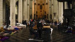 Orang-orang beristirahat di kasur dan mengobrol saat mereka menempati gereja Saint-Jean-Baptiste-au-Beguinage di Brussels, Belgia, Selasa (2/2/2021). Para imigran tanpa surat-surat resmi telah menduduki gereja untuk menarik perhatian otoritas Brussel atas penderitaan mereka. (AP Photo/Francisco Seco