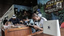 Gus In membimbing siswa saat mengikuti kegiatan belajar jarak jauh di Bank Sampah Majelis Taklim, Kecamatan Koja, Jakarta, Rabu (12/8/2020). Para sisw dapat memakai fasilitas WiFi dengan menukarkan sampah anorganik minimal 1 kilogram. (merdeka.com/Iqbal S. Nugroho)