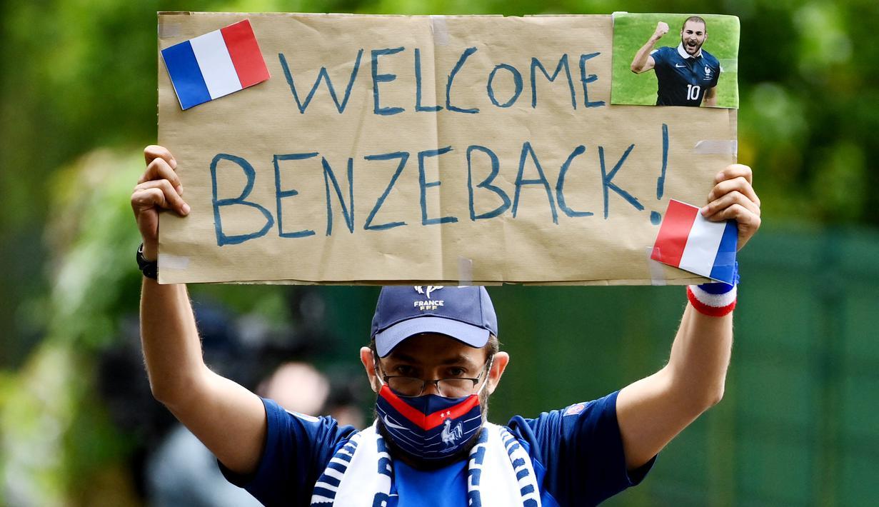 Fans menunjukan poster selamat datang kepada Karim Benzema saat sesi latihan Timnas Prancis di Clairefontaine-en-Yvelines, Rabu (26/5/2021). Benzema kembali memperkuat Timnas Prancis setelah enam tahun absen. (AFP/Franck FIfe)