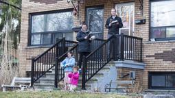 Warga memukul panci dan wajan saat menyemangati petugas medis memerangi virus corona COVID-19 di Toronto, Kanada, Minggu (29/3/2020). Aksi membuat bunyi-bunyian di luar rumah tersebut rutin dilakukan setiap sore. (Xinhua/Zou Zheng)