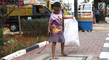 Seorang anak memungut sampah plastik di Jakarta, Rabu (12/9). Pemerintah menargetkan Indonesia bebas pekerja anak pada tahun 2022 mendatang. (Liputan6.com/Immanuel Antonius)