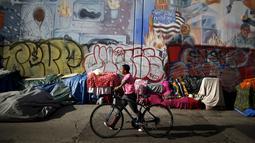 Warga berjalan melewati tenda yang ditempati kaum tunawisma di Skid Row, Los Angeles, California, Kamis (1/10/2015). Kota Los Angeles menetapkan status darurat terkait makin rumitnya persoalan kaum tunawisma di sana. (REUTERS/Lucy Nicholson)