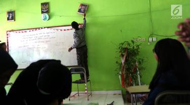 Siswa memasang pigura bergambar Wapres Jusuf Kalla di dalam kelas SMP Negeri 6 Palu, Sulawesi Tengah, Senin (8/10). Pascagempa dan tsunami Palu, siswa sekolah belum memulai aktivitas belajar mengajar. (Liputan6.com/Fery Pradolo)