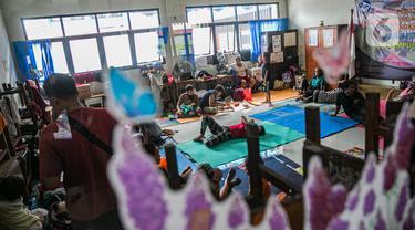 Aktivitas korban banjir di salah ruang kelas di Gedung Sekolah SDN 01/02 Kampung Melayu, Jakarta, Selasa (9/2/2021). Gedung sekolah di Kebon Pala tersebut menjadi salah satu posko pengungsian bagi sebagian korban banjir Kampung Melayu. (Liputan6.com/Faizal Fanani)