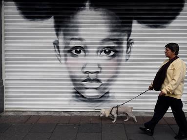 Seorang wanita berjalan melewati mural yang dilukis di pintu toko wilayah bersejarah Mexico City, Meksiko, 30 Agustus 2017. Mural tesebut sebagai bagian dari upaya pemerintah menghidupkan kembali ruang publik di wilayah kota tua. (ALFREDO ESTRELLA/AFP)