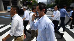 Seorang pria menyeka wajahnya saat berjalan selama gelombang panas melanda Tokyo, Jepang (1/8/2019). Badan Meteorologi Jepang (JMA) mencatat suhu tertinggi Tokyo mencapai 35,4 derajat celcius. (AFP Photo/Charly Triballeau)
