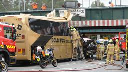 Petugas mengevakuasi penumpang dari dalam bus yang menabrak kolong jembatan kereta di Montague, South Melbourne, Australia (22/2). Belum diketahui penyebab tertabraknya bus yang mengangkut 19 orang ini. (REUTERS/Mal Fairclough)